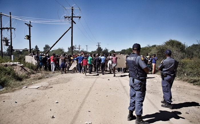 Police watch as residents continue to call for the removal of North West Premier Supra Mahumapelo on 20 April 2018. Picture: Ihsaan Haffejee/EWN