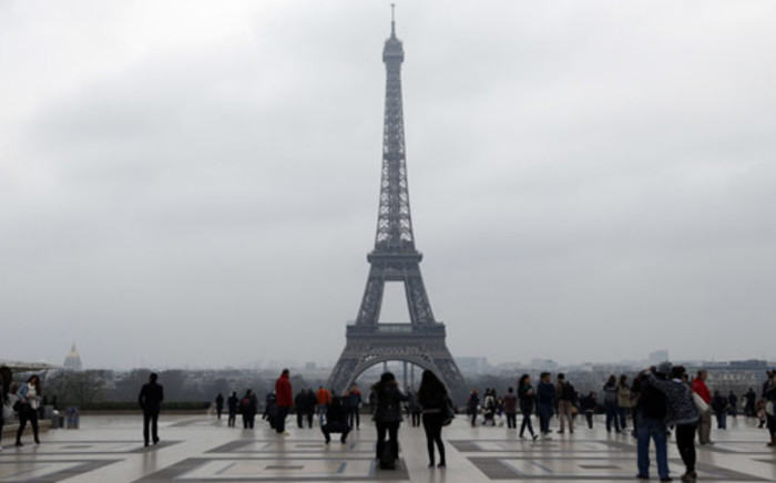 People walk on the Trocadero square in central Paris on 15 March, 2014, with the Eiffel tower in the background seen through a haze of pollution. Picture: AFP.