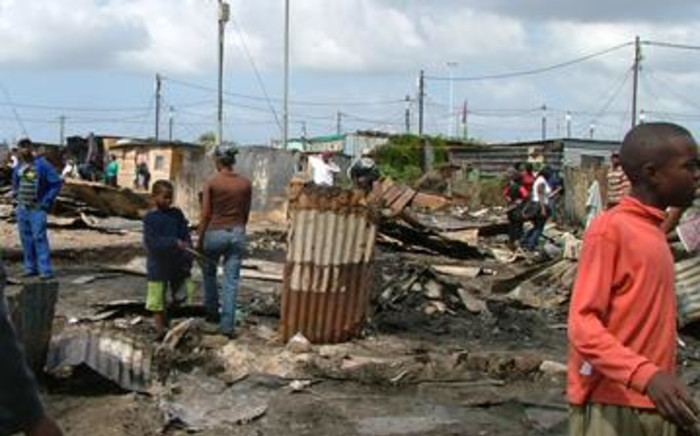 Residents from the KTC informal settlement survey the fire damage