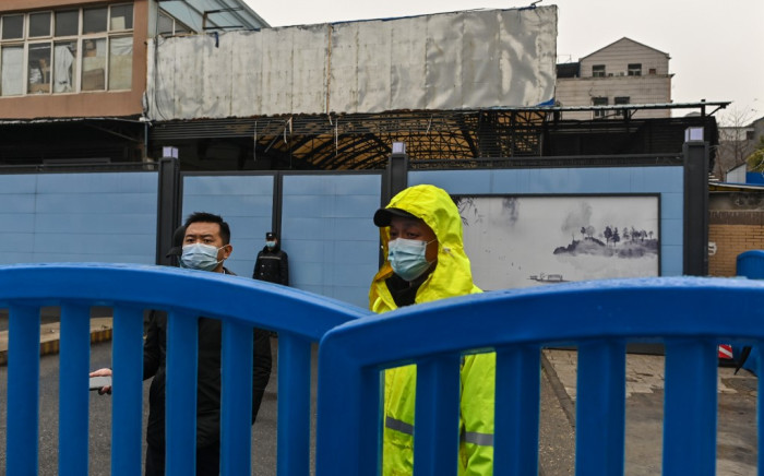 Guards stand at an entrance as members of the WHO team, investigating the origins of the coronavirus, arrive at the closed Huanan Seafood wholesale market in Wuhan on January 31, 2021. Picture: Hector Retamal/AFP.
