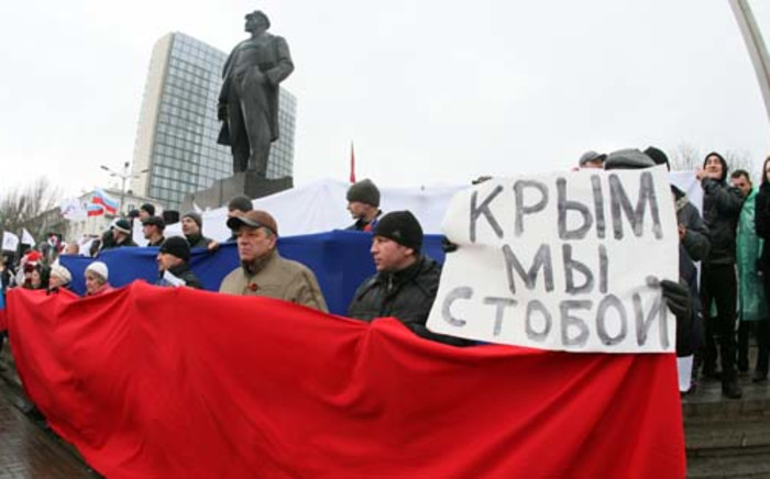 """Pro-Russian activists hold a Russian flag and a placard reading """"Crimea we are with you"""" during their rally in eastern Ukrainian city of Donetsk on March 16, 2014. Ukraine's new government and most of the international community except Russia have said they will not recognise a result expected to be overwhelmingly in favour of immediate secession. Picture: AFP."""