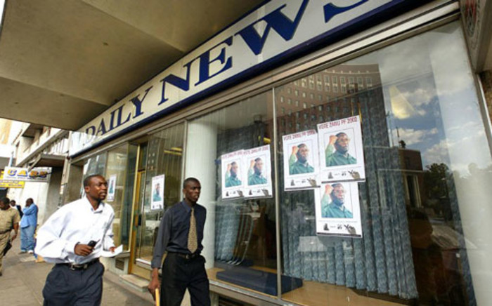 Men walk past Zimbabwean President Robert Mugabe's ruling ZANU-PF posters covering the windows of the Zimbabwean Daily News Paper in Harare on 4 March 2002. Picture: AFP