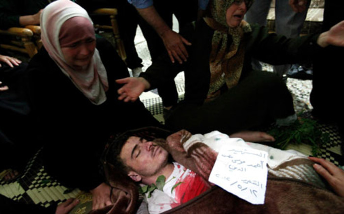 Women grieving over the body of killed Syrian Ahmed Shamseddine during his funeral in Qusayr on May 12, 2012. Picture: AFP