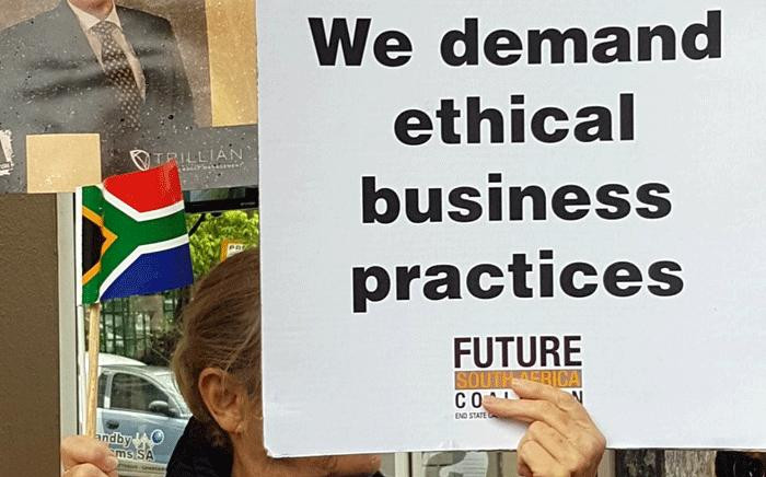 A woman holds a poster during a protest against McKinsey over 'irregular payments' involving Eskom and Trillian on 5 October 2017. Picture: Supplied.