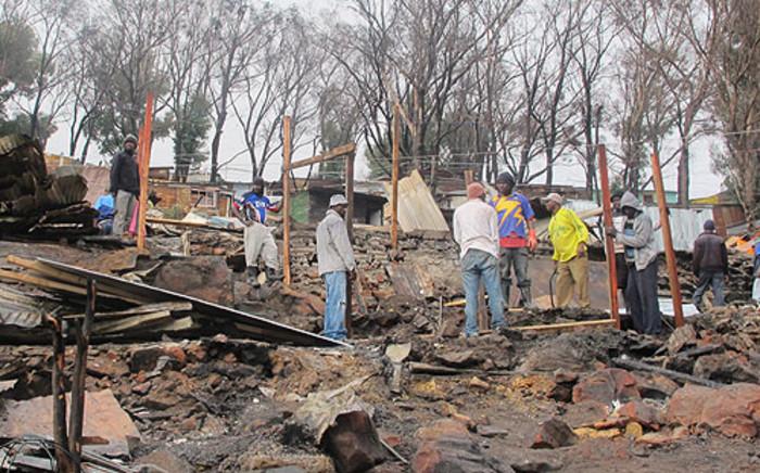 A man rebuilds his home following a deadly shack fire in Mandela Park. Picture: Georgina Selander/EWN