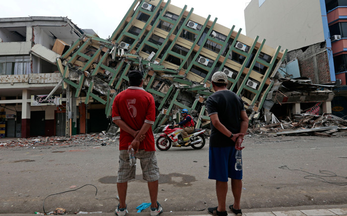 FILE. Men look at a destroyed building in the town of Portoviejo, Ecuador, on 21 April, 2016 almost a week after a powerful quake hit the country. Picture: AFP.