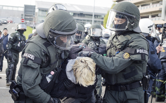 Police forces take a protestor into custody during a demonstration against a party congress of the German right wing party AfD at the Stuttgart Congress Centre ICS on 30 April, 2016 in Stuttgart, southern Germany. Picture: AFP.