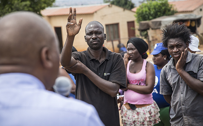 A Kaalfontein resident puts up his hand to ask DA mayoral candidate for Johannesburg Herman Mashaba a question during his visit to the community on 17 February 2016. Picture: Reinart Toerien/EWN.
