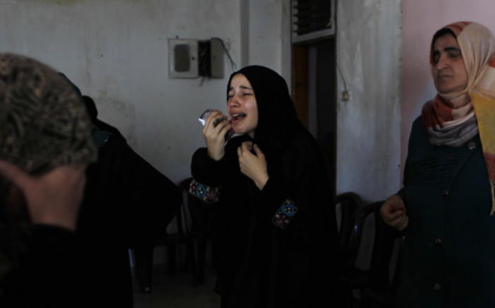 Relatives and friends mourn near the body of Hazem Abu Shamalah (unseen), who was killed in shelling after the Israeli military resumed its assault on Gaza, during his funeral in Khan Yunis, in the southern Gaza Strip, 27 July, 2014. Picture: AFP