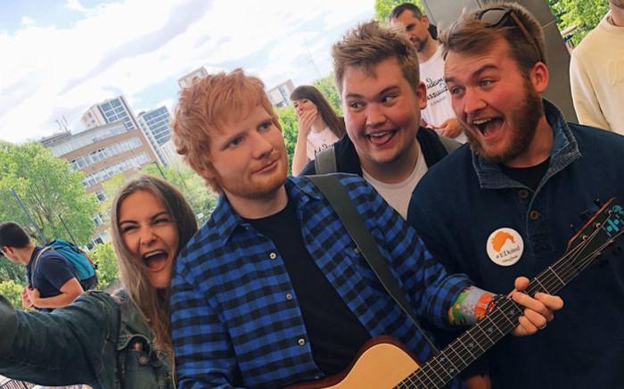 FILE: Fans gather around a wax figure of British musician Ed Sheeran at Madame Tussauds in London. Picture: @MadameTussauds/Twitter