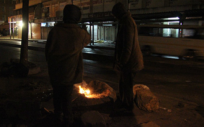 Homeless men keep themselves warm by burning news papers in the Joburg CBD. Picture: Taurai Maduna/EWN.
