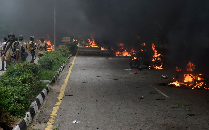 Indian security personnel (L) stand near burning vehicles set alight by rioting followers of a religious leader convicted of rape in Panchkula on 25 August 2017. Picture: AFP