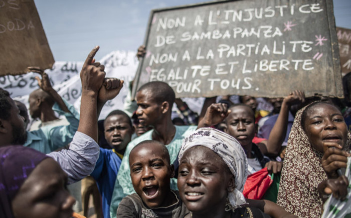 "A protester holds a placard reading ""No to the injustice of Samba Panza, No to partiality, Equality and freedom for all"" as residents demonstrate in the 'Muslim enclave' of the PK5 district in Bangui to express their anger on 31 May, 2014. Picture: AFP."