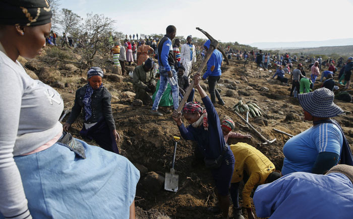 A woman uses a pick axe to dig as hundreds of others search for what they believe to be diamonds on 15 June 2021 after the recent discovery of unidentified stones at KwaHlathi village near Ladysmith in KwaZulu-Natal. Picture: Phill Magakoe/AFP