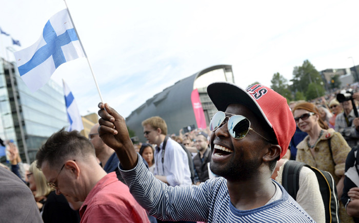 Participant of a demonstration called 'We have a Dream, Multiculturalism is not a nightmare' waves a Finnish flag in Helsinki, Finland, on 28 July, 2015. Picture: AFP.