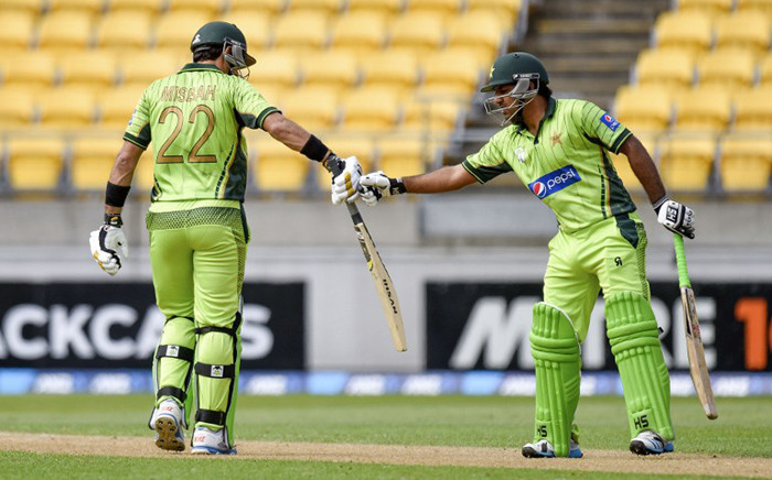 Misbah-ul-Haq (L) captain of Pakistan is congratulated by teammate Sarfraz Ahmed of Pakistan as he celebrates 50 runs during the first one-day international cricket match between New Zealand and Pakistan at Westpac Stadium in Wellington on 31 January, 2015. Picture: AFP