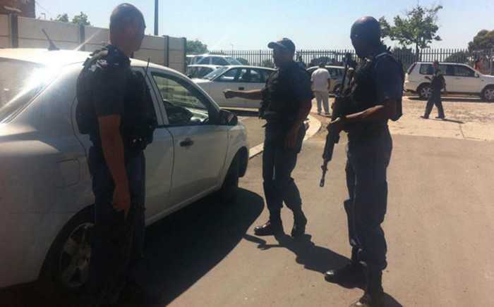Armed Manenberg police officers are stationed near the house where a woman and her son were shot on 14 October 2014. Picture: Carmel Loggenberg/EWN.