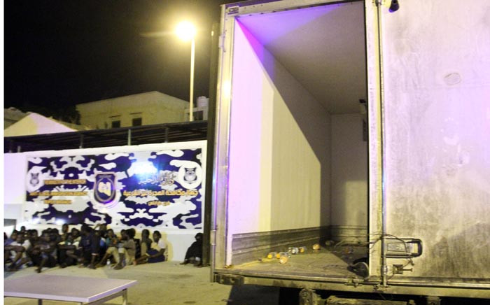 Men from African countries sit in Tripoli on 4 June 2017 next to a truck which was used to carry illegal migrants in the area of the coastal town of Guarabouli, 60 kilometres east of the Libyan capital. Picture: AFP.