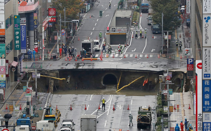 A giant sinkhole is seen in a four-lane urban boulevard, exposing support columns of nearby buildings at a traffic intersection in Fukuoka, southwestern Japan, on 8 November, 2016. Picture: AFP.