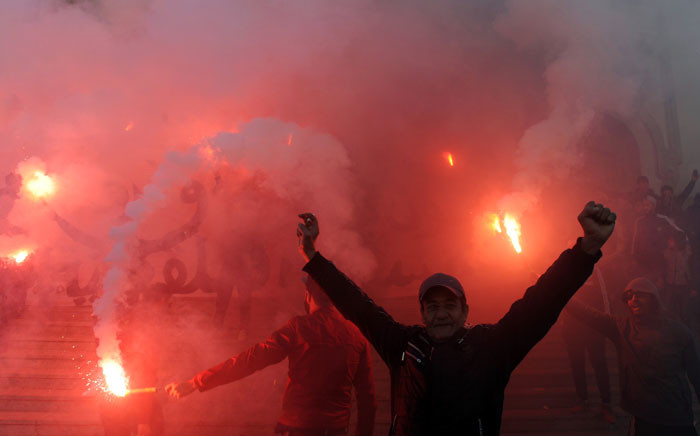 Tunisians carry flares and shout slogans against the government in Tunis, on 14 January 2018, during a demonstration over price hikes and austerity measures. Picture: AFP