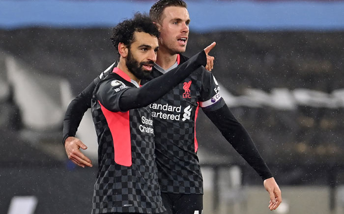 Liverpool's Mohamed Salah (L) celebrates with teammate Jordan Henderson (R) after scoring their second goal during the English Premier League football match between West Ham United and Liverpool at The London Stadium, in east London on 31 January 2021. Picture: Justin Setterfield/AFP