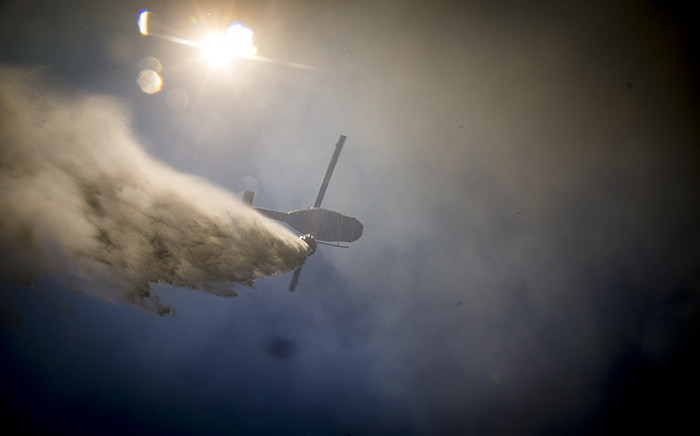A helicopter drops water on a veld fire in Ocean View. Picture: Thomas Holder/EWN