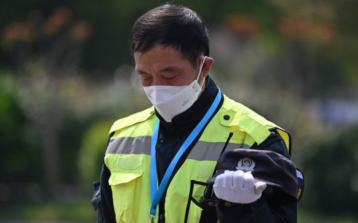 Police officers and officials stop and pay their respects during a three-minutes of silence to mourn those who died in the fight against the pandemic along a street in Wuhan, in China's central Hubei province on 4 April 2020. Picture: AFP