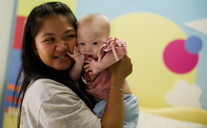 Thai surrogate mother Pattaramon Janbua (L) holds her baby Gammy, born with Down Syndrome, at the Samitivej hospital, Sriracha district in Chonburi province on 4 August 2014. Picture: AFP.