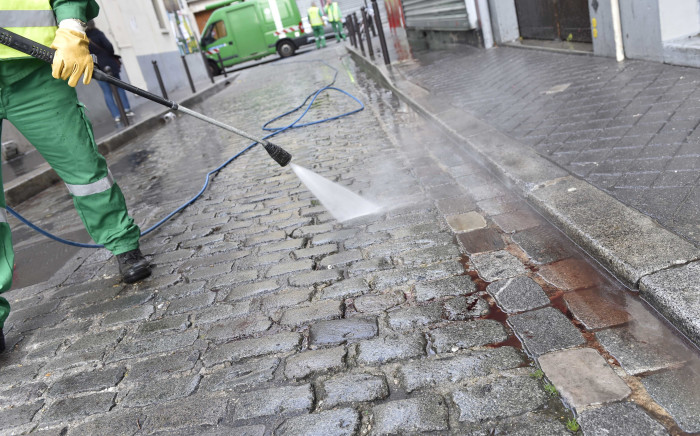 A street cleaner arrives to clean blood from the pavement near a patisserie at the Rue de Charonne in Paris on November 14, 2015, following a series of coordinated attacks in and around Paris late Friday which left more than 120 people dead. Picture: AFP