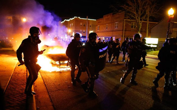 Police in riot gear move past a vehicle that continues to burn on the street in Ferguson, Missouri, on 24 November 2014. Picture: EPA