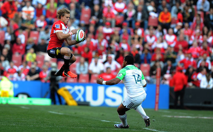 Lions' Andries Coetzee (L) jumps with the ball past Highlanders' Waisake Naholo during the Super XV rugby semi-final match between Lions and Highlanders at Ellis Park on July 30, 2016 in Johannesburg, South Africa. Picture: AFP.