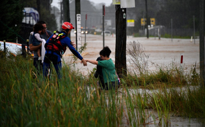 """A rescue worker helps residents cross a flooded road during heavy rain in western Sydney on March 20, 2021, amid mass evacuations being ordered in low-lying areas along Australia's east coast as torrential rains caused potentially """"life-threatening"""" floods across a region already soaked by an unusually wet summer. Picture: AFP"""