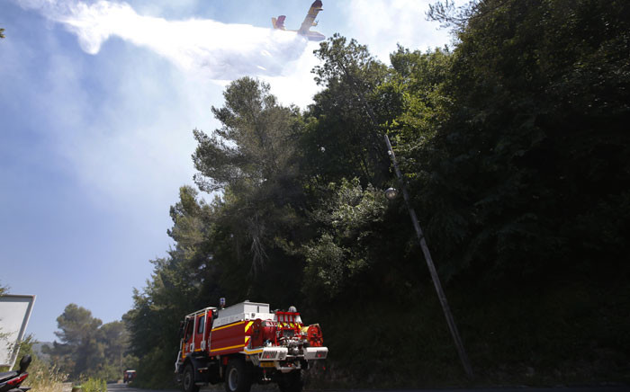 A Canadair aircraft drops water as firefighters try to extinguish a forest fire in the city of Nice, French Riviera, on June 28, 2015. Picture: AFP.