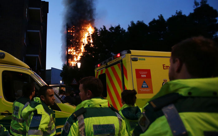 Members of the emergency services watch as Grenfell Tower is engulfed by fire on June 14, 2017 in west London. Picture: AFP.