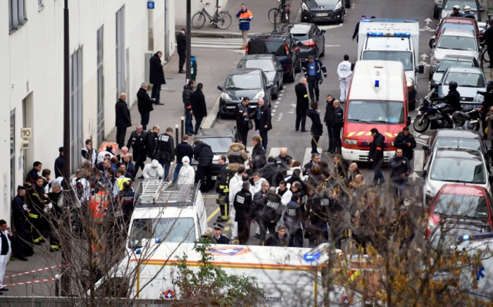 A general view shows firefighters, police officers and forensics gathered in front of the offices of the French satirical newspaper Charlie Hebdo in Paris on 7 January, 2015. Picture: AFP.
