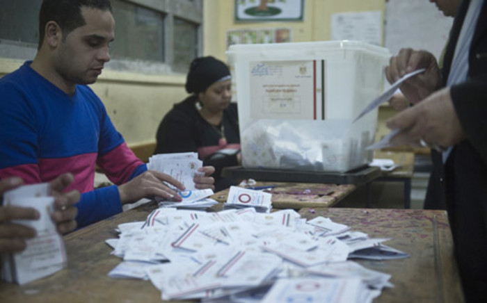 Polling station officials count ballots in the Egyptian capital Cairo on 15 January 2014 at the end of the second day of voting in a referendum on a new constitution. Picture: AFP.