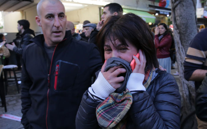 A woman reacts at the scene of an attack by an unidentified gunman, who opened fire at a pub in Tel Aviv killing two people and wounding five others on 1 January 2016. Picture: AFP/Daniel Bar On.