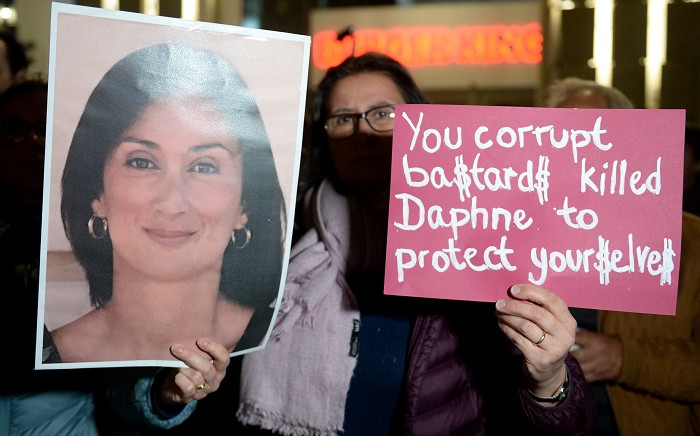 A protestor holds up a portrait of killed reporter Daphne Caruana Galizia during a gathering for the second day outside the Parliament building in Valletta, on 27 November 2019, the day after several political resignations in the wake of the Daphne Caruana Galizia murder investigation. Picture: AFP