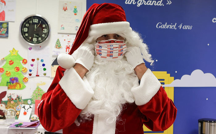 A man dressed as Santa Claus puts a face mask on at the Libourne's post office, southwestern France, on 10 December 2020. Picture: AFP
