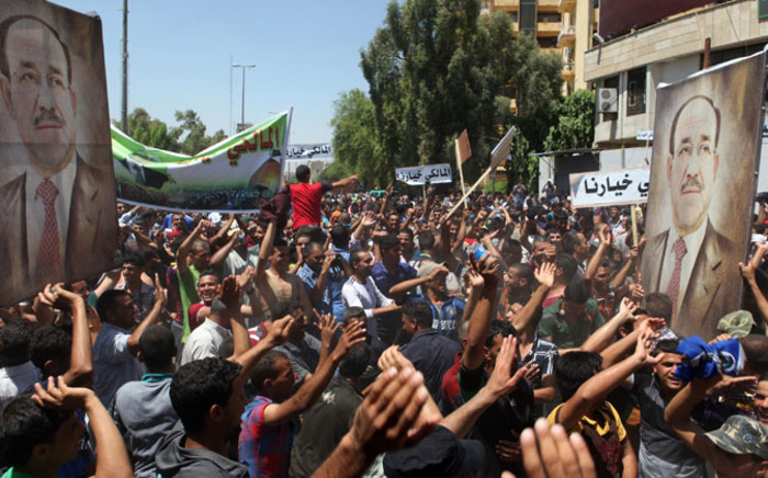 FILE: Iraqis hold giant portraits of Iraq's Prime Minister Nuri al-Maliki during a demonstration to support him on 11 August, 2014. Picture: AFP