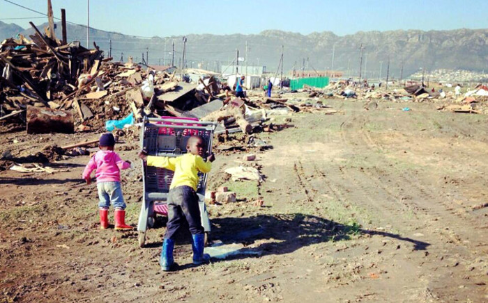 FILE: Children in Nomzamo searching through rubble trying to source material to rebuild their house on 13 June 2014. Picture: Carmel Loggenberg/EWN.