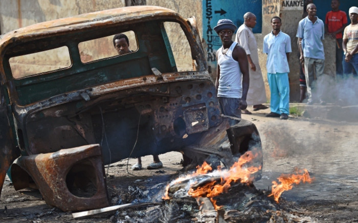 Protesters opposed to Burundian President Pierre Nkurunziza's third term stand beside a burning vehicle during a demonstration in the Buyenzi neighborhood of Bujumbura on 26 May, 2015. Picture: AFP.
