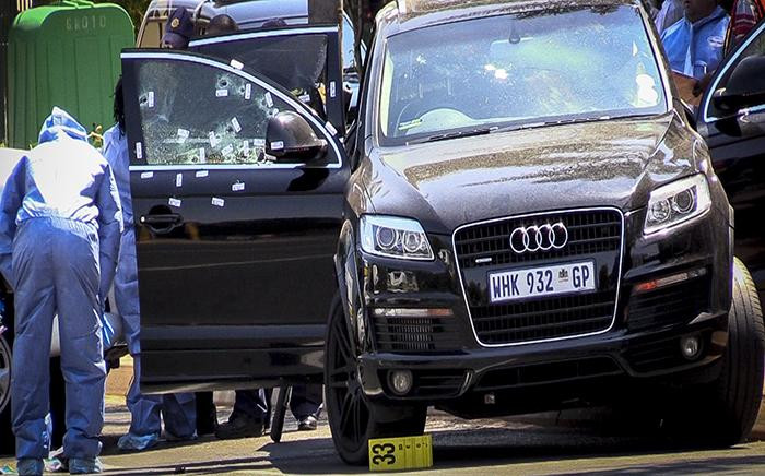 """FILE: An Audi is riddled with bullet holes on the scene where Lebanese drug dealer Sam """"Black"""" Issa was gunned down in a drive-by shooting in Bedfordview on 12 October 2013. Picture: Reinart Toerien/EWN"""