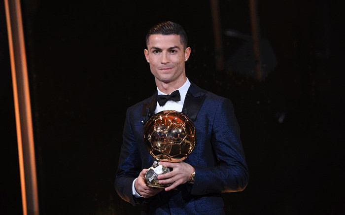 This handout photo released on 7 December 2017 by L'Equipe shows Portugese player Cristiano Ronaldo posing with the Ballon d'Or France Football trophy in Paris. Picture: AFP.