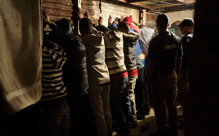 FILE: A group of men stand with their hands against the wall after the house where they were gambling in was raided during a combined Metro Police and SAPS operation in Manenburg. Picture: AFP.