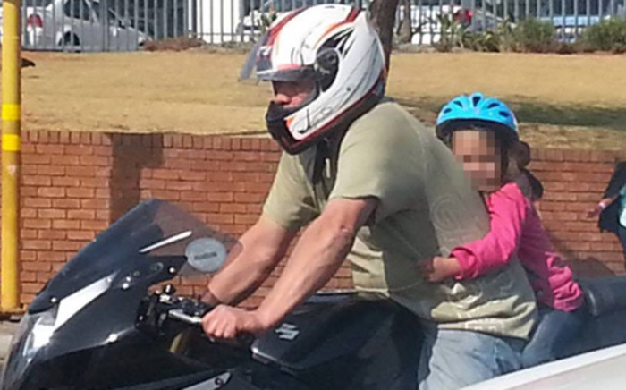 This screenshot from a video posted on YouTube shows a motorbike rider on an Edenvale road with a small girl, wearing only a bicycle helmet, clinging to his back. Picture: YouTube