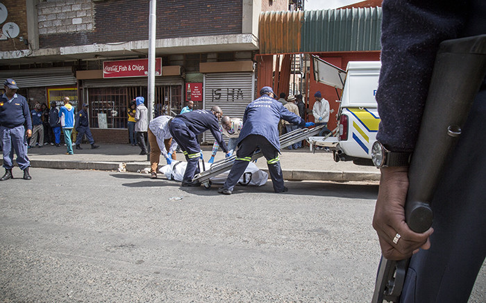 Forensic pathologists load the bodies of two South African males that were shot dead in a hostel in Jeppestown on 18 April 2015. Picture: Thomas Holder/EWN.