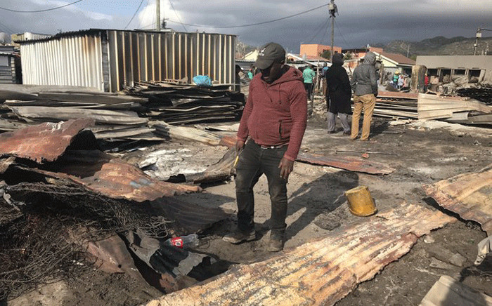 A resident walks through the rubble after a shack fire in Masiphumelele on 29 July 2019. Picture: Monique Mortlock/EWN.