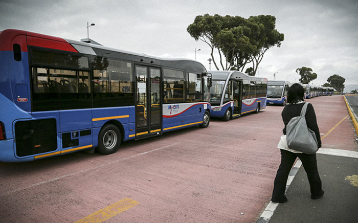 A pedestrian passes by the line of MyCiti Buses parked as part of the protest in the red designated bus lane. Picture: Thomas Holder/EWN