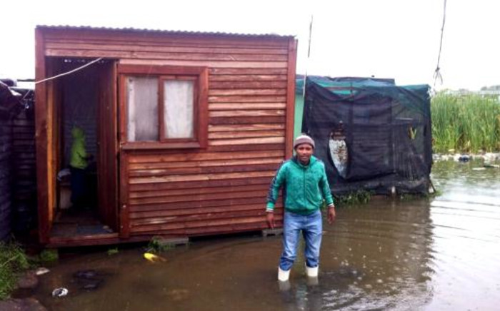 A Gugulethu resident stands in the water left by heavy rains overnight on 16 September 2013. Picture: Mia Spies/EWN.